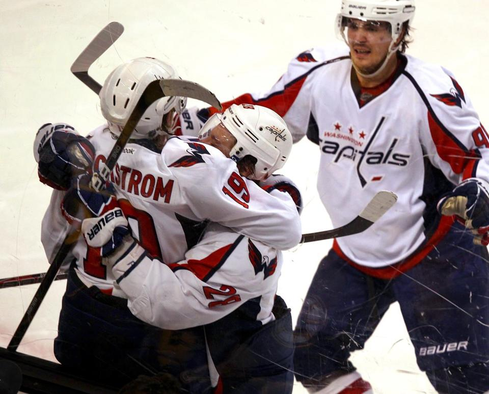 Nicklas Backstrom (top) is mobbed by teammates after giving the Capitals the win in double overtime.