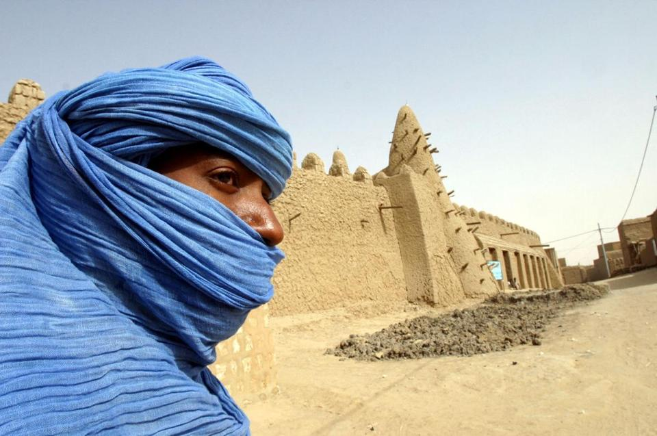 A Tuareg nomad stands near a 13th-century mosque in Timbuktu.