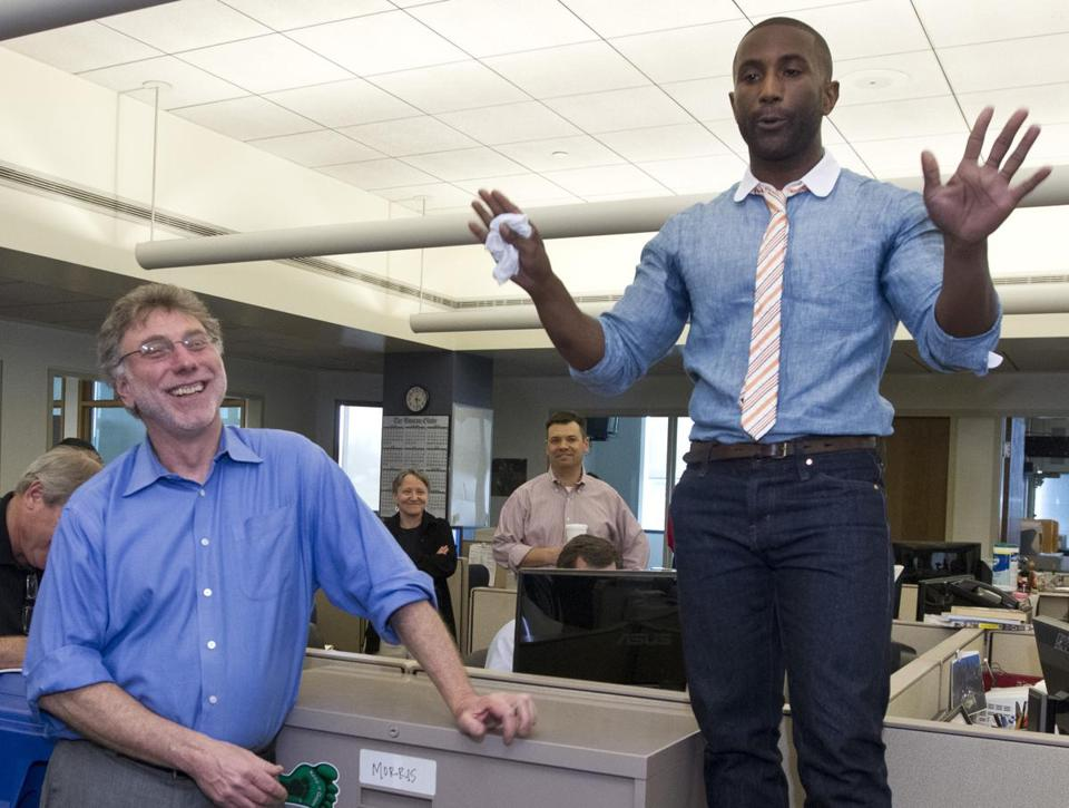Boston Globe editor Martin Baron, left, with Wesley Morris, the paper's film critic who was awarded the 2012 Pulitzer Prize for criticism, during an announcement ceremony in the newsroom.