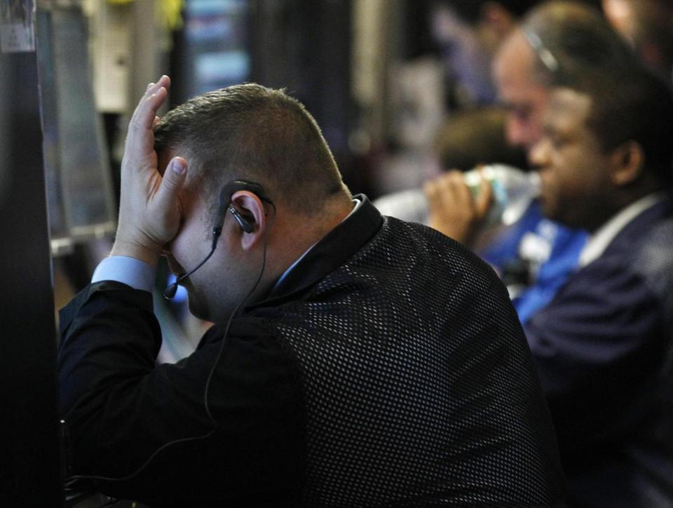 A trader placed his hand on his face on the floor of the New York Stock Exchange Monday.
