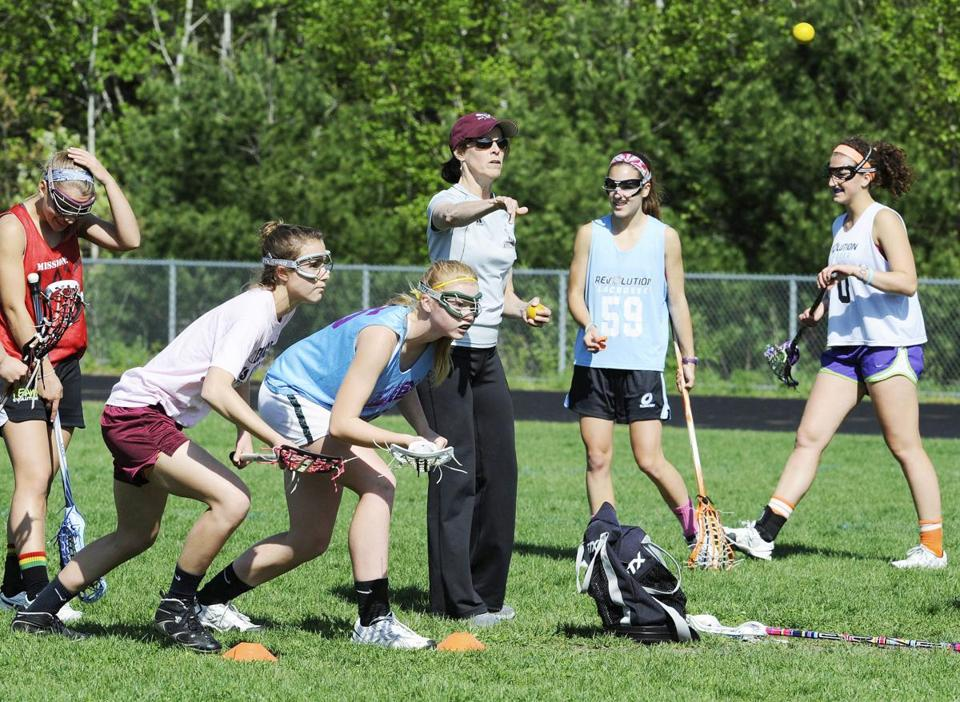 Westford Academy coach Julie Devlin-Olivier tosses out a ball at a Monday practice.
