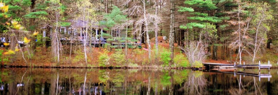 The Maxwell Mays Cottage sits under a canopy of pine and oak trees on Carr Pond.