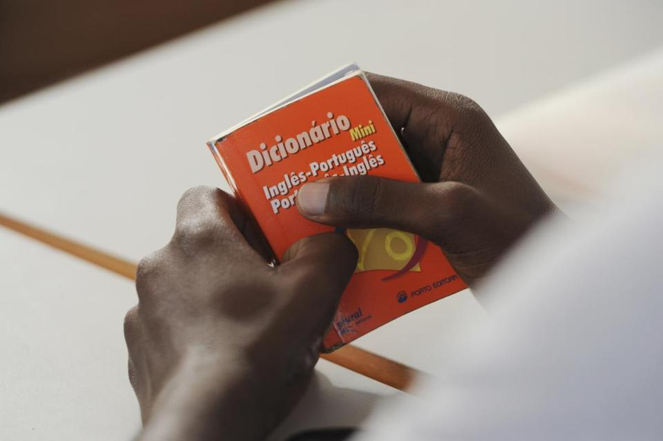A student holds a Portuguese- English dictionary.