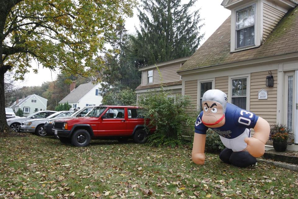 Fans attending a Patriots game parked in the front yard of a North Street residence in October 2009. Foxborough's Town Meeting voted to put an end to the practice Monday.