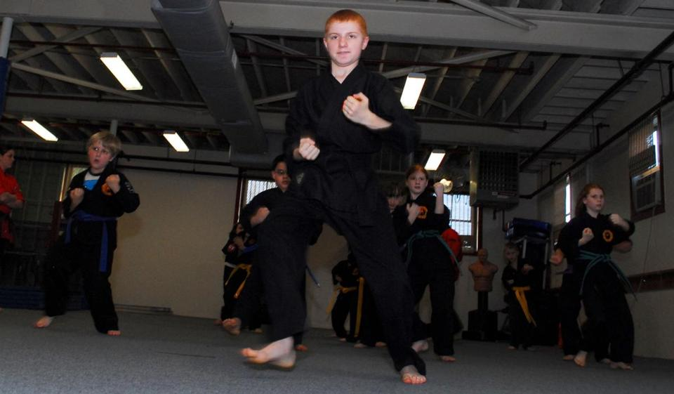 Steven McDonough, a black belt in karate, leads students at Bridgewater Martial Arts. Below (from left), Kids Action Initiative founders Maureen Hancock and John Hatfield and sensei Meghan Boyle.