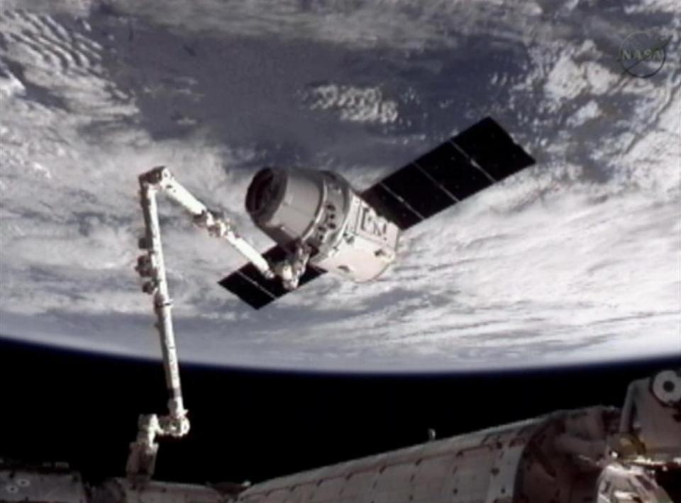 This image from NASA-TV shows the SpaceX Dragon capsule grappled by the robotic arm connected to the International Space Station.