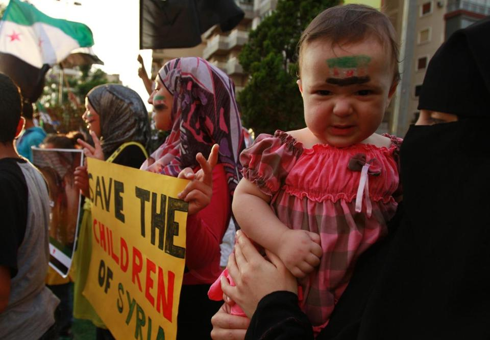 A child with a Syrian opposition flag painted on the face was held Saturday during a protest by Syrian refugees in Tripoli.