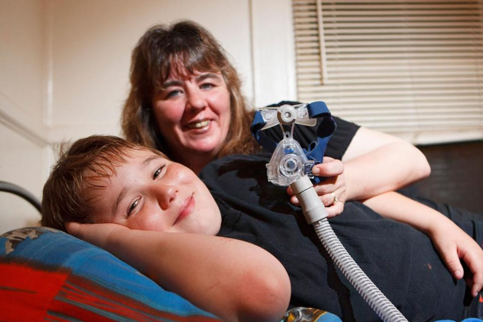 Justin Colamaria with his mom, Tina Foye, and the breathing machine that helps his sleep apnea.