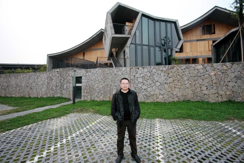 Chinese architect Wang Shu stands in front of the Xiangshan campus of the China Academy of Art.