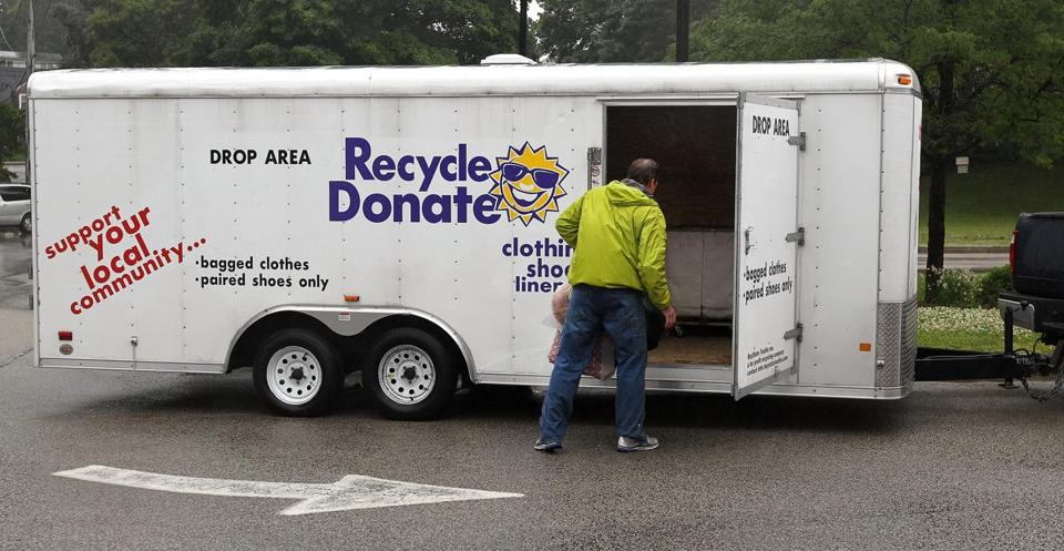 Bay State Textiles employee Steven Hansen picks up clothing left in the company's drop box at the Academy Avenue School in Weymouth.