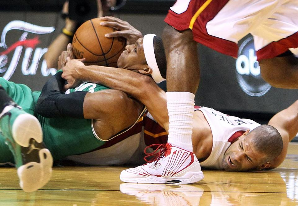 Rajon Rondo risked floor burns and a poke in the eye as he wrestled a loose ball to his chest, keeping it out of the reach of the Heat's Shane Battier (right). The Celtic guard eventually got a pass off.