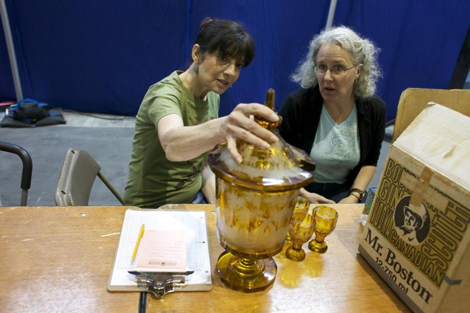 "Marsha Bemko (left) looks over items brought to the Convention and Exhibition Center last Saturday by one of thousands of ""Antiques Roadshow"" hopefuls."