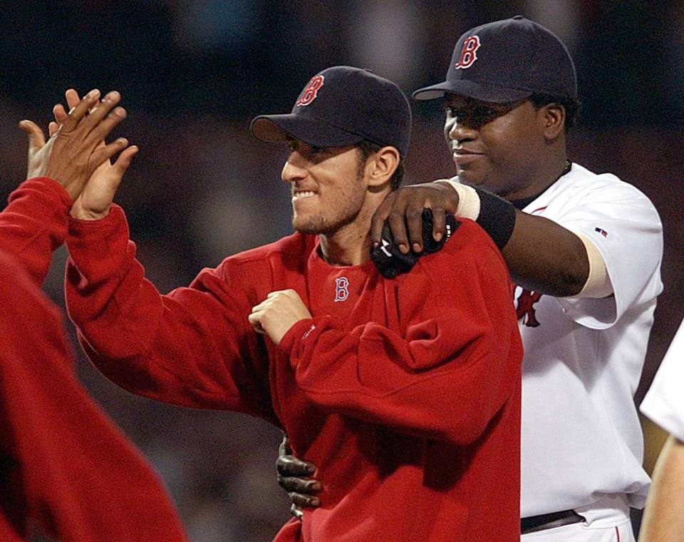Nomar Garciaparra gets a high five from Pedro Martinez while David Ortiz pats him on the back after his 5-for-5 performance.