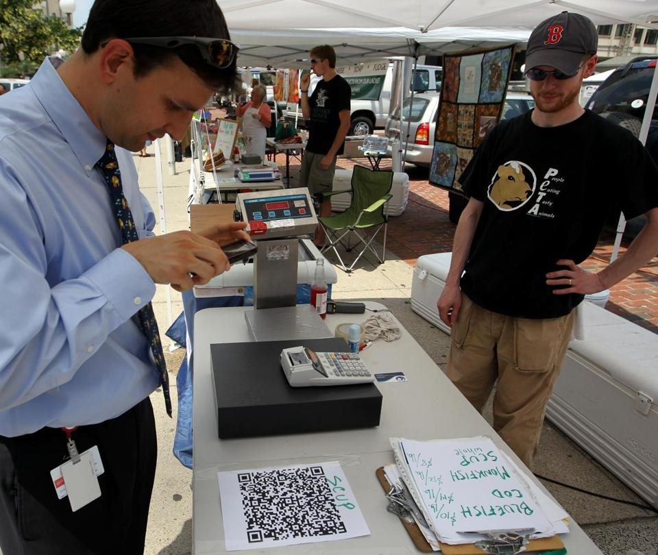 Joe Forte used a QR code and a smartphone app to learn more about fish and other items sold at Red's Best at a recent farmers market in Boston.