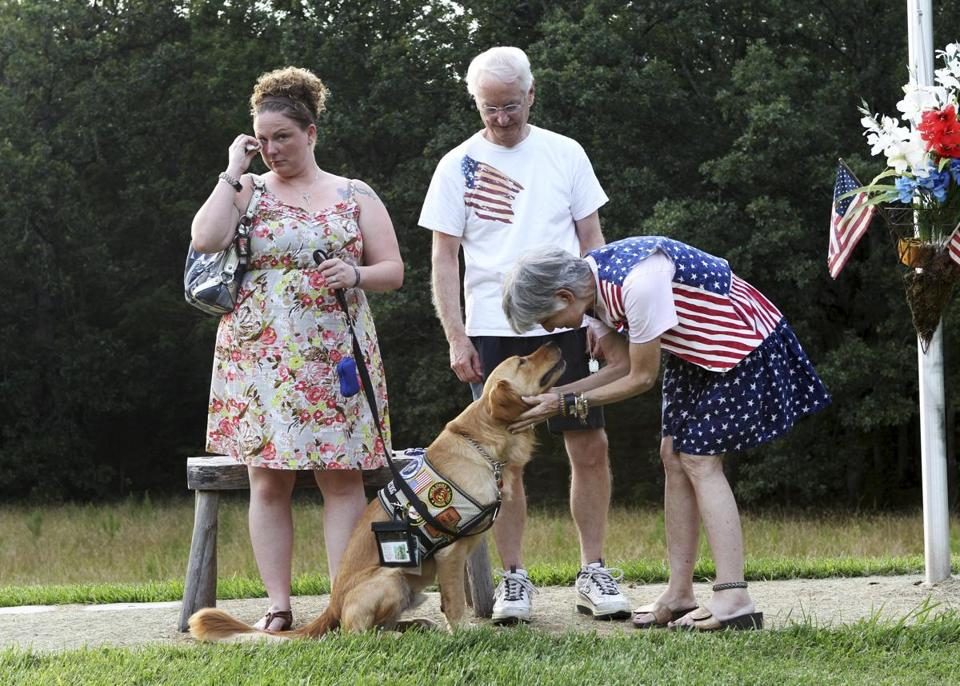 Lexington , NC -- 06/15/12- - Samuel and Evelyn Harris take Natasha and her service dog Josh to a memorial they have created for their son Joshua, a Navy Seal who died in Afghanistan. The service dog is named in honor of Josh. Natasha was invited to the Harris home to learn more about her dog's namesake. Patriot Rovers, the NC organization that trains and places the service dogs, names them after fallen soldiers . They have seen the dogs help the gold star families heal knowing they are aiding troubled vets returning to civilian life. ( Joanne Rathe / Globe Staff section: business metro topic: 22vetdog reporter: Katie Johnson Chase )