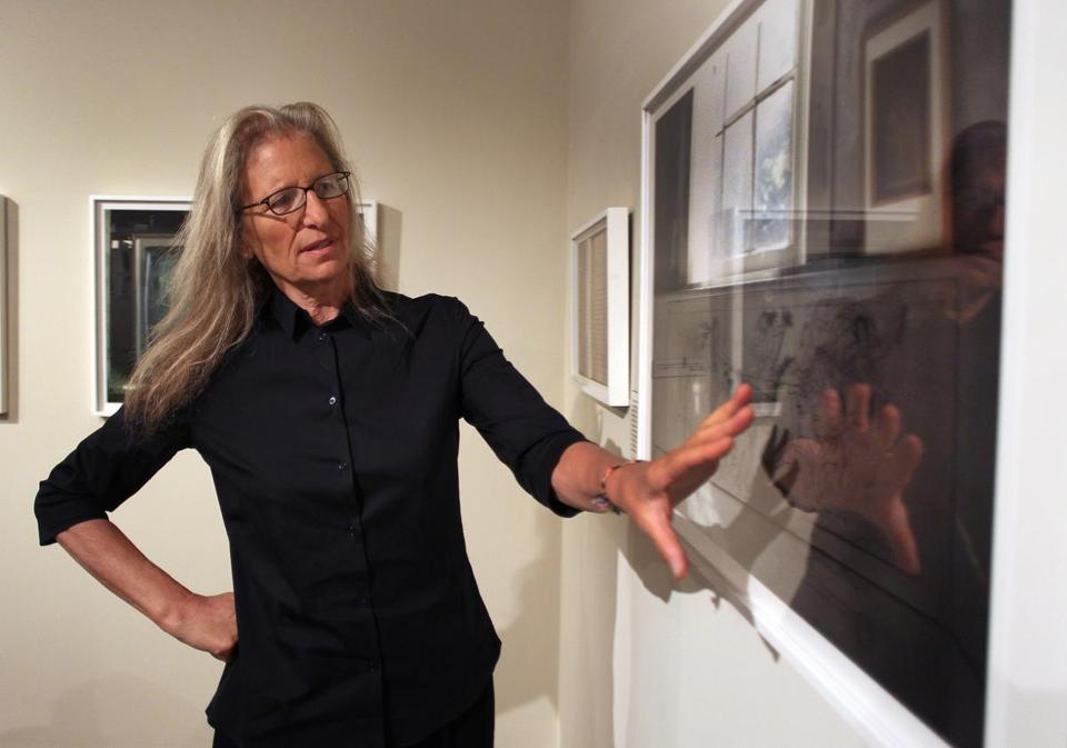 "Annie Leibovitz looks at her photograph ""May Alcott's drawing on her bedroom wall, Orchard House, Concord, Massachusetts, 2010"" on display in the exhibit ""Pilgrimage"" at the Concord Museum."
