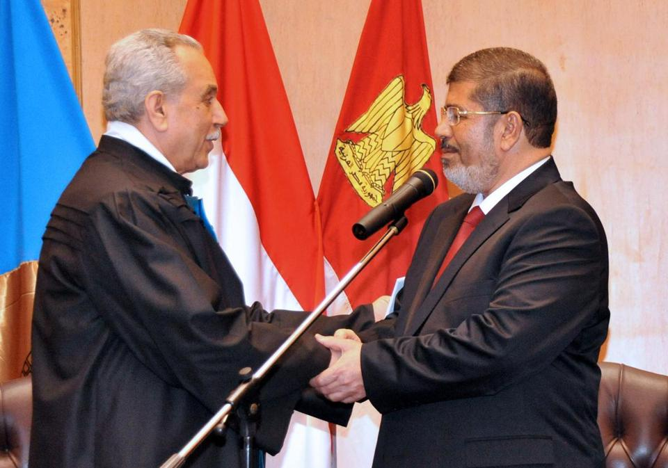"""In this handout picture made available by the Egyptian presidency on June 30, 2012, Egyptian President Mohamed Morsi (R) shakes hands with Faruq Sultan, head of the presidential election commission, after taking the oath of office at his swearing-in ceremony at the Constitutional Court in Cairo to become the country's first freely elected leader and its first president since Hosni Mubarak's overthrow last year. AFP PHOTO / HO ==RESTRICTED TO EDITORIAL USE - MANDATORY CREDIT """"AFP PHOTO /EGYPTIAN PRESIDENCY """" - NO MARKETING NO ADVERTISING CAMPAIGNS - DISTRIBUTED AS A SERVICE TO CLIENTS==-/AFP/GettyImages"""