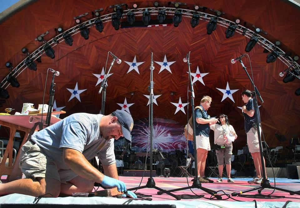 Scenic artist Joshua Wells applied final touches to the Hatch Shell on Tuesday while others checked camera angles in preparation for Wednesday's July Fourth concert and festivities on the Esplanade.