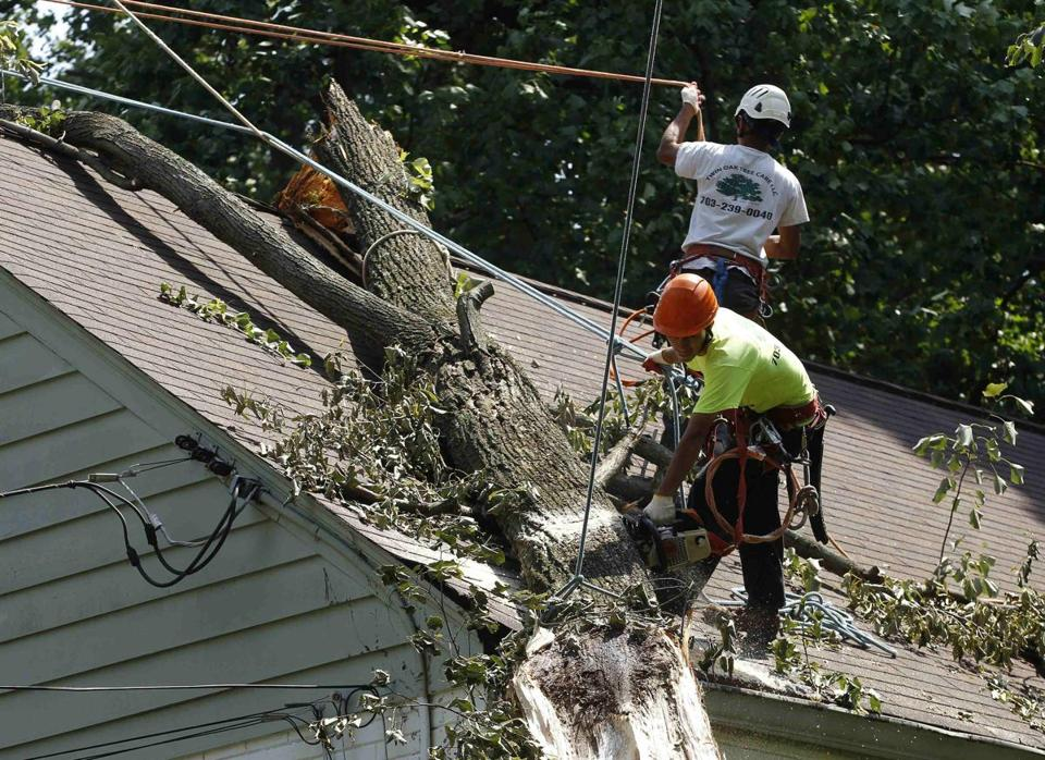 A work crew removed a fallen tree Tuesday from a roof in Silver Spring, Md. More repair crews arrived from Quebec.