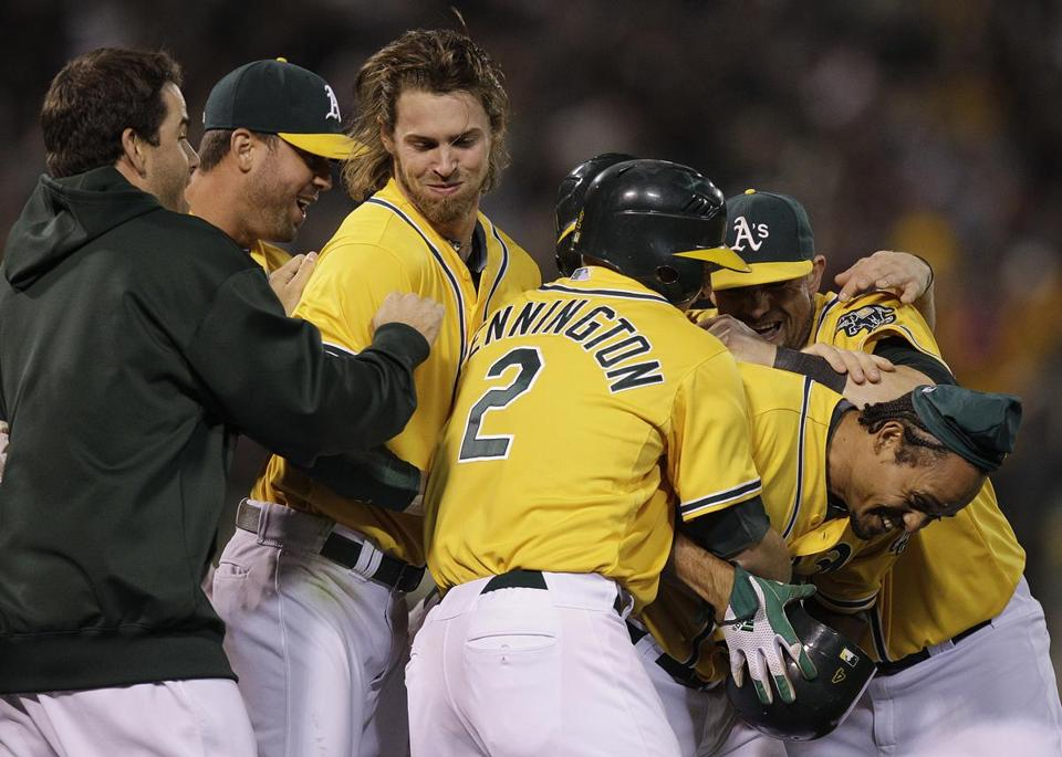 The Athletics mobbed Coco Crisp, right, after he hit the game-winning sacrifice fly in the ninth inning.