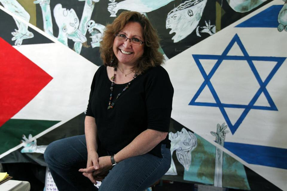 Debbie Nathan, founder and executive director of Artsbridge Inc. at her home in front of art work by the kids in Artsbridge.