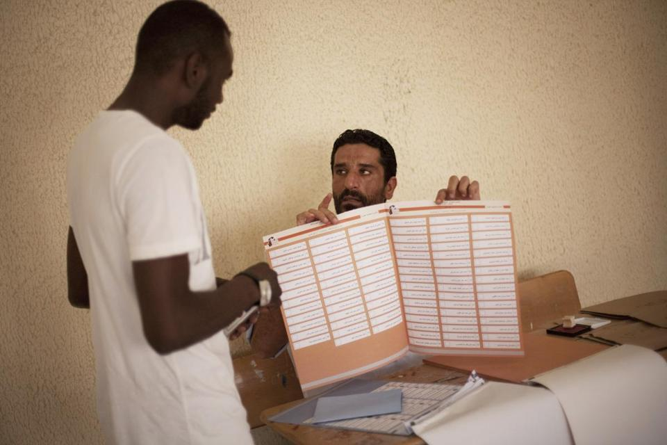 An election official showed a man how to fill out a ballot at a polling station in Tripoli, and a demonstrator for greater
