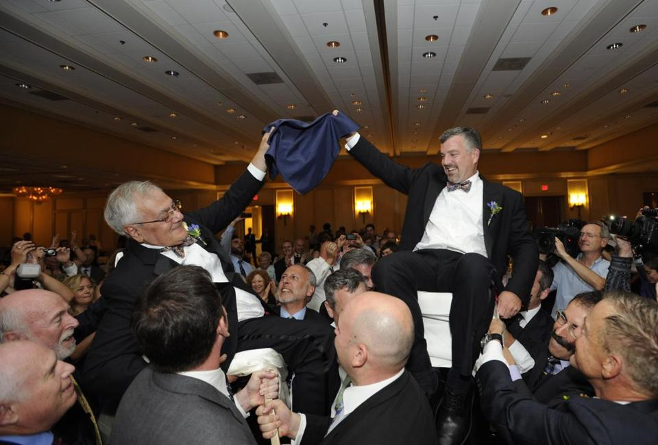 Barney Frank (left) and Jim Ready are hoisted above the crowd on chairs at their weekend wedding.