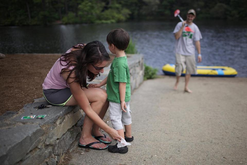 Chelsea Smith applied an extra dose of insect repellent on her son, Luke, 3, after rafting on Johnson Pond in Raynham.