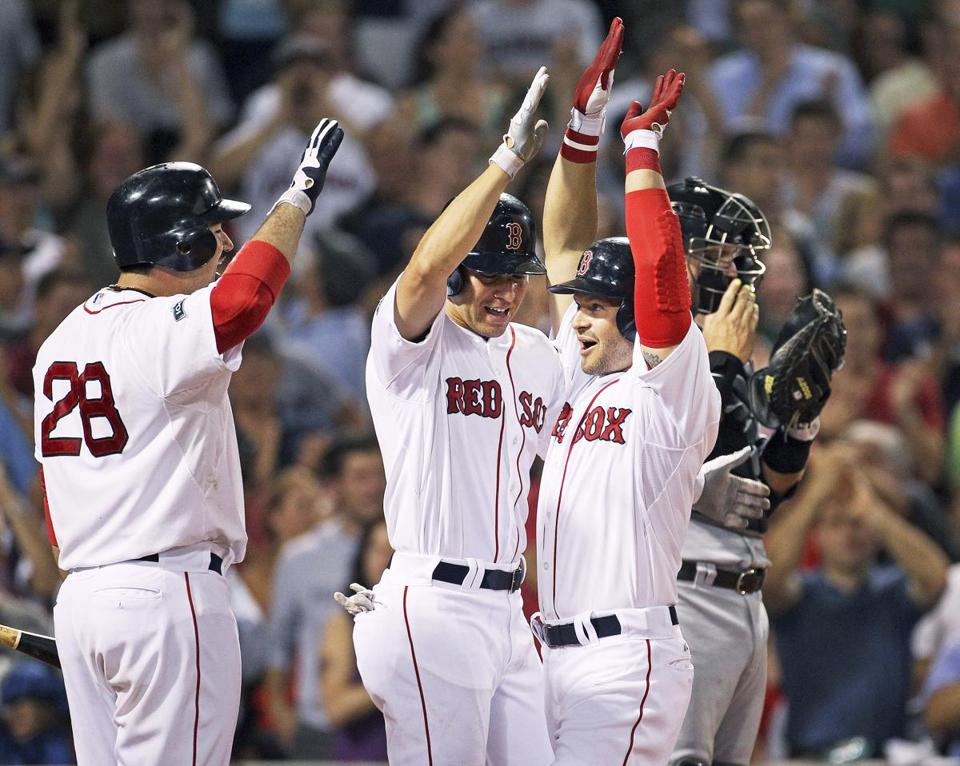 Red Sox' Cody Ross (right) gets up in arms as he celebrates with Jacoby Ellsbury and Adrian Gonzalez (28) after hitting the second of his two home runs.