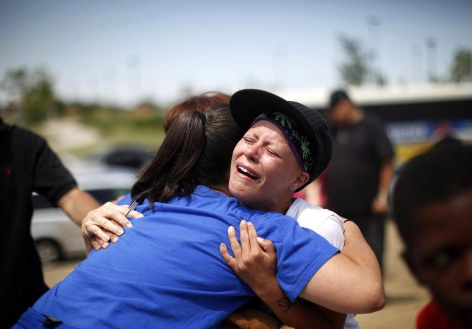Mourners embraced near the memorial created where 12 people where killed July 13 in movie theater in Aurora, Colo.