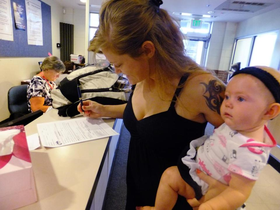 Laura Fritz, 27, said she grew up in a wealthy family, but their fortunes changed. Fritz, shown with her daughter, filled out forms at an assistance center outside Denver recently.