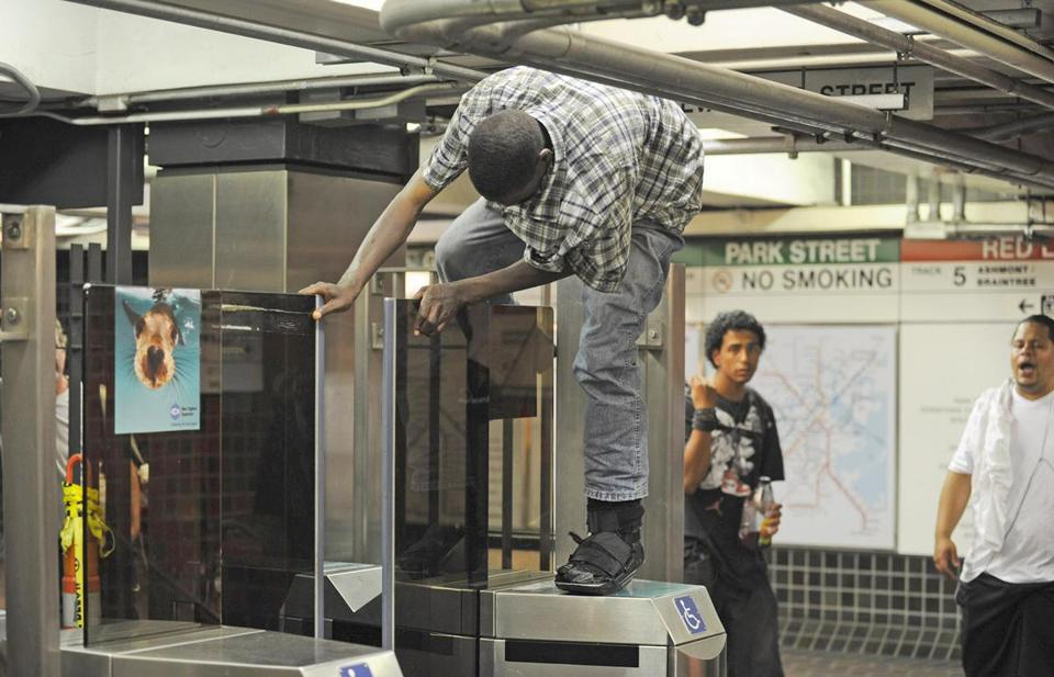 A T rider jumps over a turnstile to avoid paying fare.