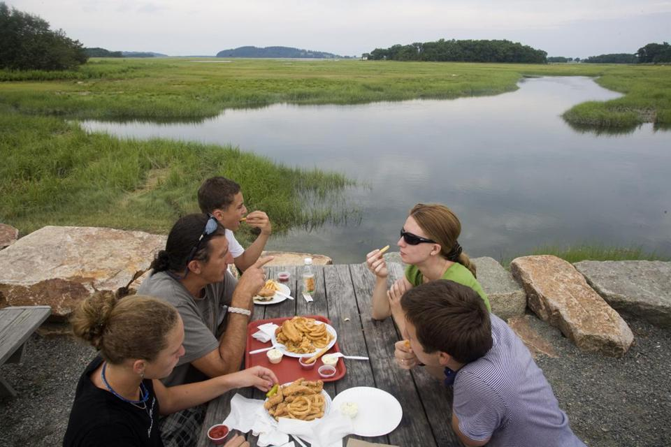 Patrons ate clams and fries at a picnic table next to the water outside J.T. Farnham's in Essex.