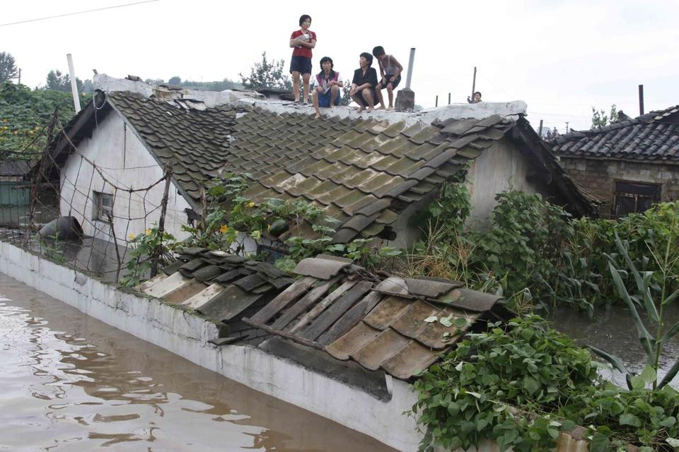 People waited on the roof of a house Monday in Anju, one of the North Korean cities hardest hit by flooding.