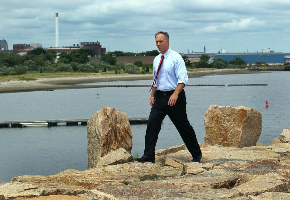 Mayor Jon Mitchell walks on New Bedford's hurricane dike near the proposed location (in background) of a wind-energy staging facility.