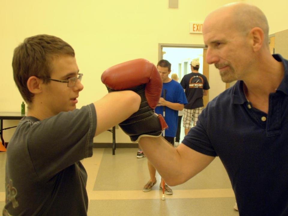 Brockton's Scott Fedor instructs Aaron Rawley of Hudson on martial arts at a self-defense class at the Carroll Center for the Blind.