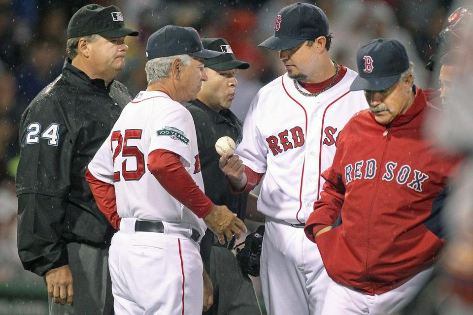 Josh Beckett hands the ball to manager Bobby Valentine after summoning medical personnel to the mound in the third inning. Beckett was forced to leave with a back spasm.