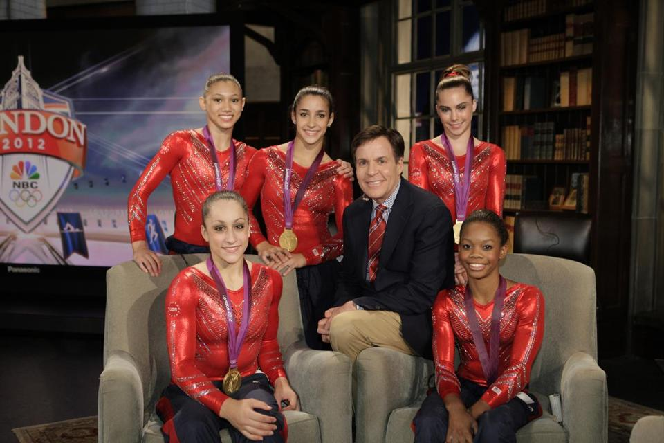Bob Costas, shown the US women's gymnastics team, has been hosting NBC's prime time Olympics show, when the network is broadcasting recorded events from earlier in the day.