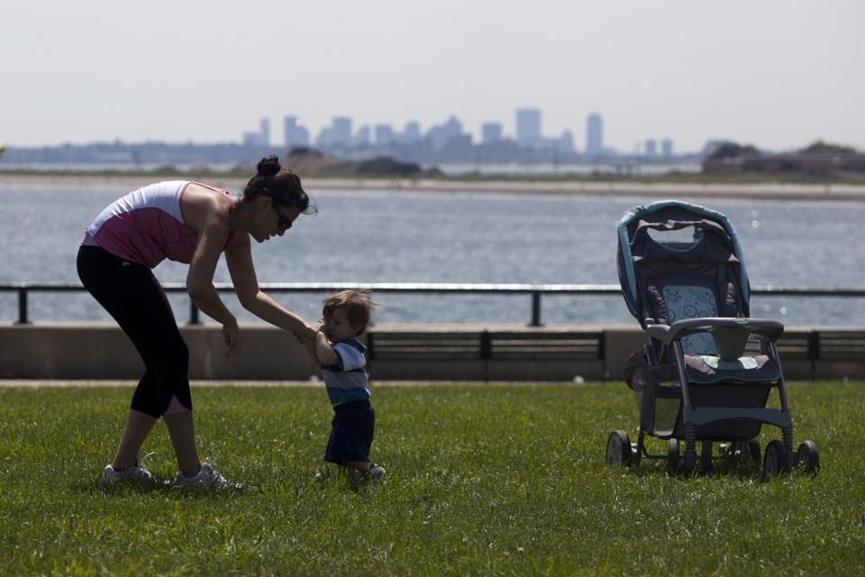 Iva Dochi helped her 14-month-old son, Arber, practice walking at Red Rock Park in Lynn.