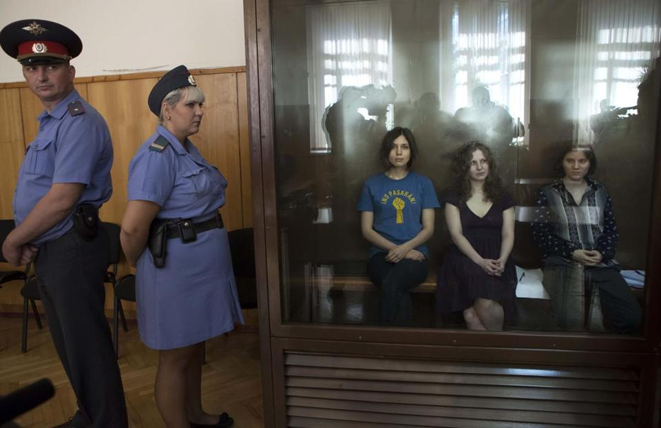 Three feminist punk rockers — from left in glass cage, Nadezhda Tolokonnikova, Maria Alekhina and Yekaterina Samutsevich— wait at a courtroom in Moscow Wednesday.