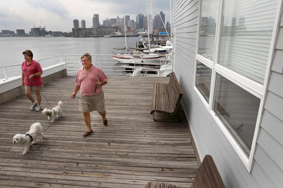 Linda and Dennis Chateauneuf walk their dogs, Lucy and Charlie, near their Charlestown home. They moved from a 5,200-square-foot house in Concord to a two-bedroom in Charlestown.