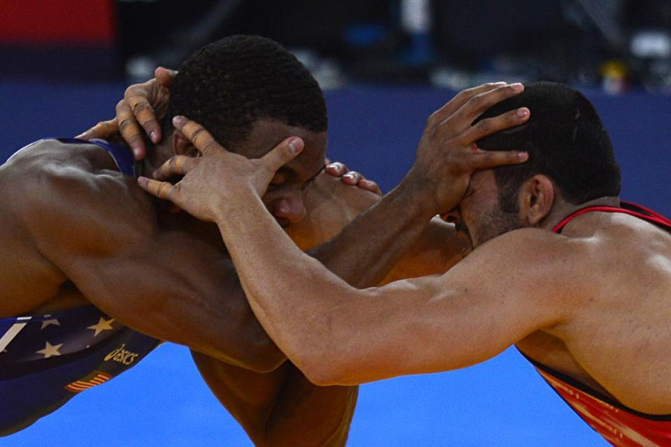 Jordan Burroughs (left) beat Iran's Sadegh Saeed Goudarzi to earn the Americans the first gold medal in wrestling.