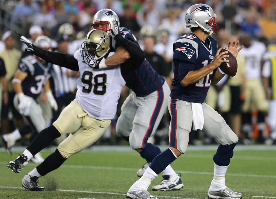 Tom Brady (right) played only two series, and Patriots tackle Nate Solder used any means necessary to protect him from the Saints' Sedrick Ellis.