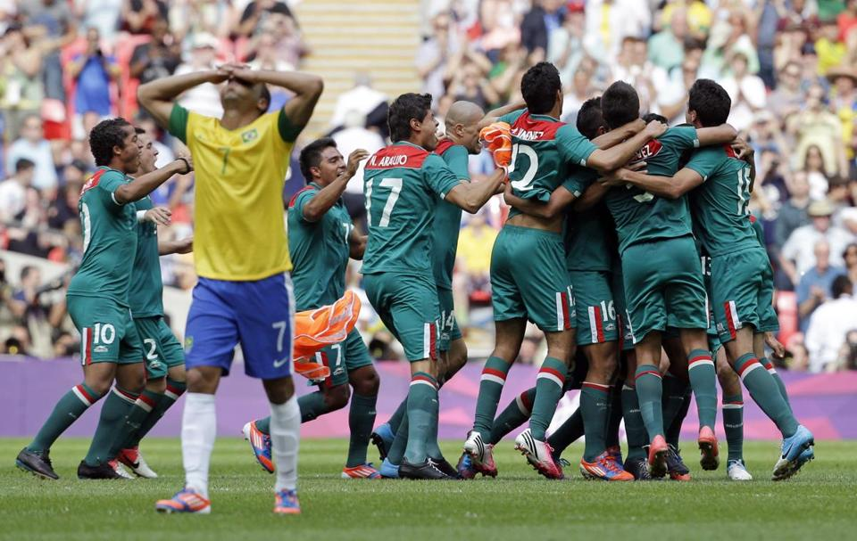 Brazil's Lucas (7) walks off dejectedly as Mexico's players begin to celebrate their gold medal in soccer after a 2-1 victory.