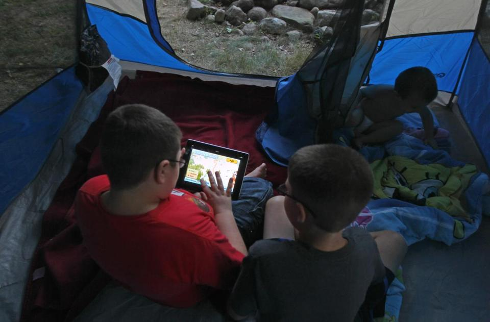 John Lawson and Ethan Kelleher played with an iPad in their tent at Bay View Campground in Bourne.