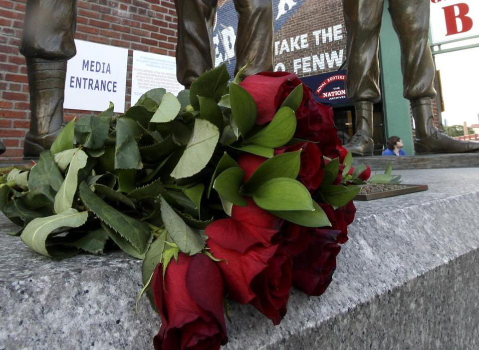 "Roses were placed at the feet of Johnny Pesky on the ""Teammates"" statue outside Fenway Park Monday."