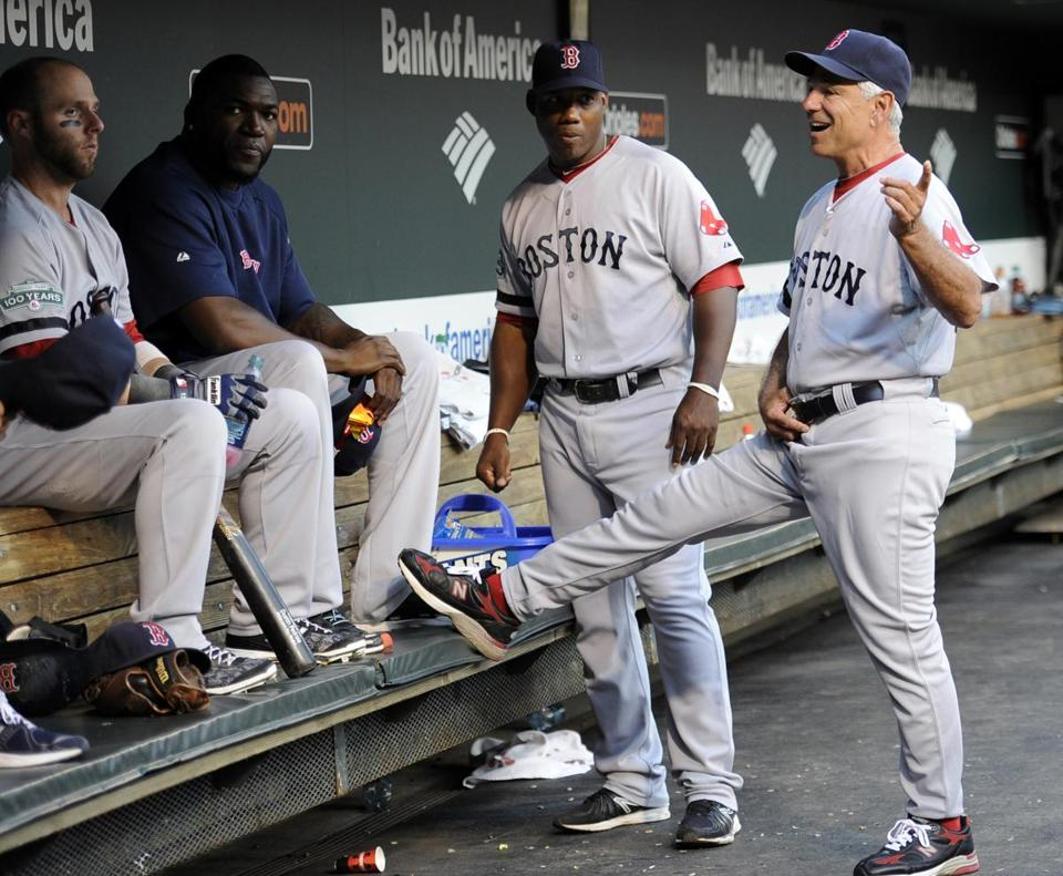 Boston Red Sox manager Bobby Valentine, right, talks with, from left, Dustin Pedroia, David Ortiz and first base coach Alex Ochoa in the dugout before a baseball game against the Baltimore Orioles, Tuesday, Aug. 14, 2012, in Baltimore. (AP Photo/Nick Wass)