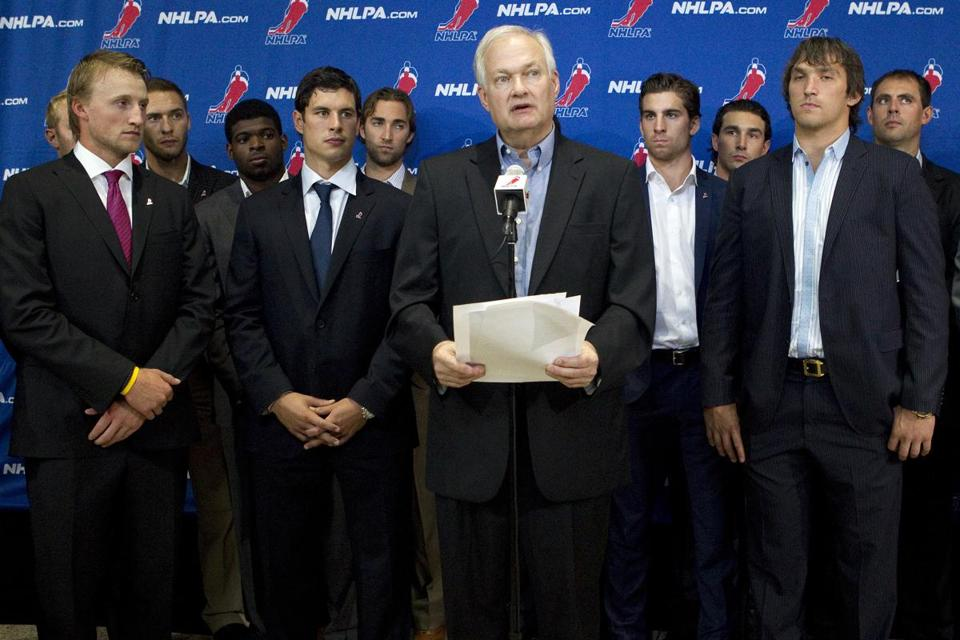 Donald Fehr, center, executive director of the NHL Players' Association, stood with NHL players and spoke with reporters following collective bargaining talks Tuesday in Toronto.