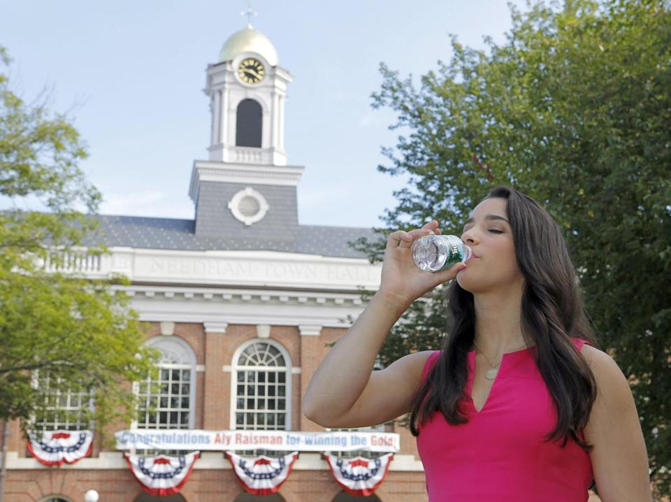 Aly Raisman drank water outside Needham Town Hall, where she announced a partnership with Poland Spring.