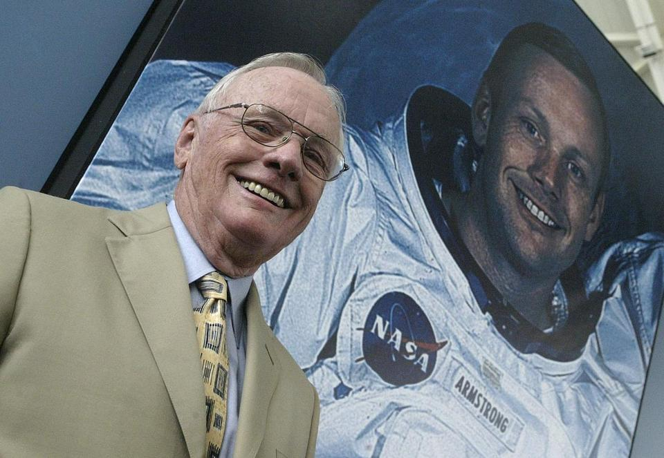 US austronaut Neil Armstrong posed in front of his photo during a visit to Spain in this July 26, 2005 file photo.